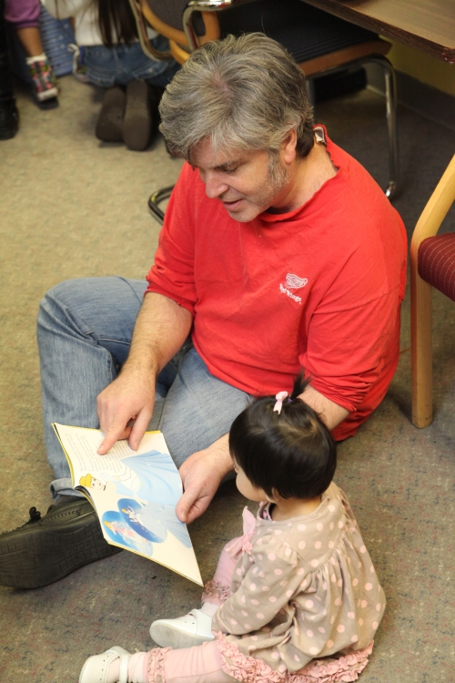 Michael reads to a child at FLOC's Sixth Annual Book Festival.
