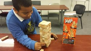 Julian plays Jenga before the start of the tutoring program.