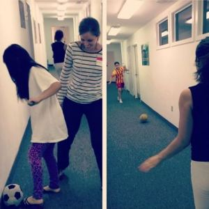 Students and their tutors play soccer.